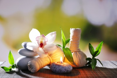 Spa composition with herbal massage bags, candle and bamboo on t